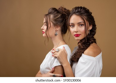 Two young beautiful girls in trendy jewellery. Sexy carefree women posing on mustard wall background with necklace, silver jewelry. Fashion gorgeous beauty. Models with Earrings.