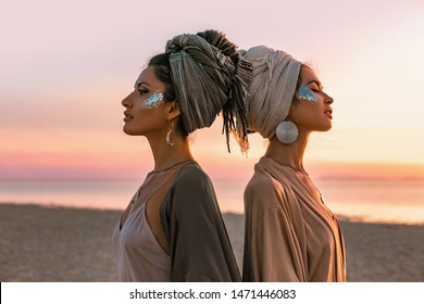 two young beautiful girls in turban on the beach at sunset