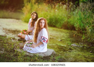 two young beautiful girls in white shirt with floral ornament with wreaths in their hands sitting on the background of the river. The celebration of the pagan Slavic holiday of Ivan Kupala Day or