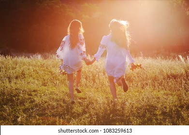 two young beautiful girls in white shirts with floral ornament with flower wreaths in their hands run against the background of nature and grass in the contour or the back light of the sun. The