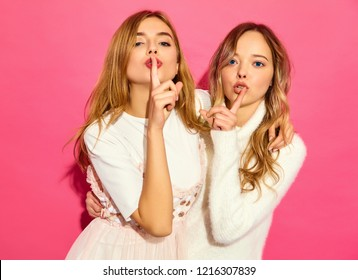 Two young beautiful hipster girls in trendy summer white clothes. Sexy carefree women posing near pink wall. Models finger showing hush silence sign, gesture