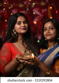 Two young and beautiful Indian Bengali women in Indian traditional dress are holding a Diwali diya/lamp in their hands in front of colorful bokeh lights. Indian lifestyle and Diwali celebration