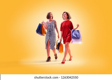 Two young beautiful lady walking after successful shopping. they smile and carry colour packages in their hands. colour background