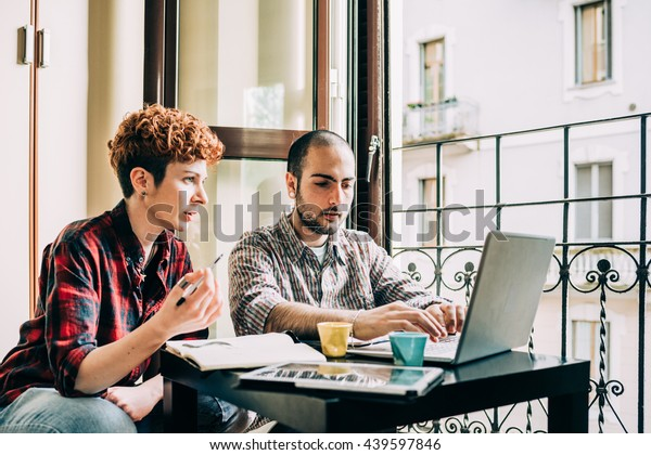 Two young beautiful man and woman working indoor in house using computer, talking to each other - work, business, technology concept
