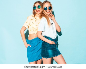 Two young beautiful smiling blond hipster girls in trendy summer jeans skirts clothes. Sexy carefree women posing near blue wall in round sunglasses. Positive models having fun and hugging