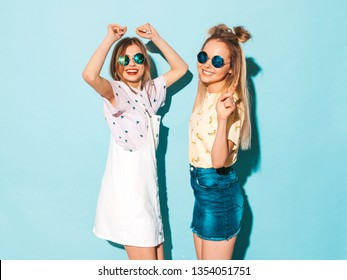 Two young beautiful smiling blond hipster girls in trendy summer colorful T-shirt clothes. Sexy carefree women dancing near blue wall in round sunglasses. Positive models having fun