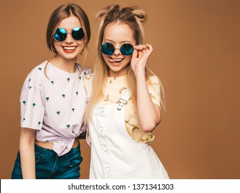 Two young beautiful smiling blond hipster girls in trendy summer colorful T-shirt clothes. Sexy carefree women posing near beige wall in round sunglasses. Positive models having fun