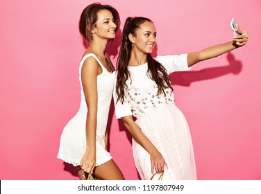Two young beautiful smiling hipster girls in trendy summer clothes. Sexy carefree women posing near blue wall. Positive models making selfie on smartphone