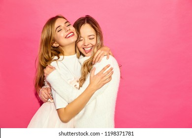 Two young beautiful smiling hipster girls in trendy summer white clothes. Sexy carefree women posing near blue wall. Positive models hugging