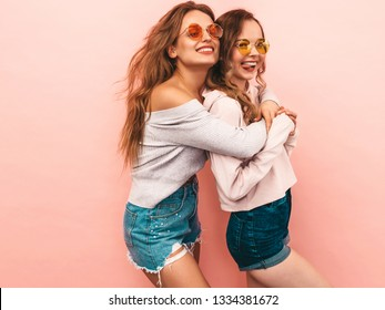 Two young beautiful smiling hipster girls in trendy summer hipster clothes. Sexy carefree women posing on pink background. Positive models having fun