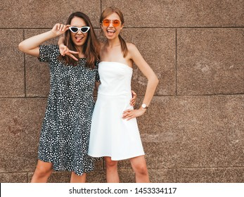 Two young beautiful smiling hipster girls in trendy summer dresses. Sexy carefree women posing in the street near brown wall.Positive models having fun in sunglasses