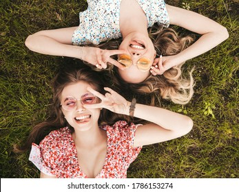 Two young beautiful smiling hipster girls in trendy summer sundress.Sexy carefree women lying on the green grass in sunglasses.Positive models having fun.Top view.They show peace sign - Shutterstock ID 1786153274