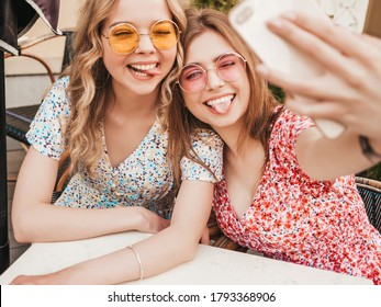 Two young beautiful smiling hipster girls in trendy summer sundress.Carefree women chatting in veranda cafe on the street background.Positive models having fun and and taking selfie on smartphone