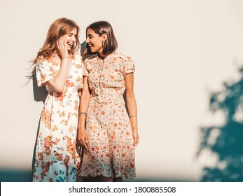 Two young beautiful smiling hipster girls in trendy summer sundress.Sexy carefree women posing near wall on the street background. Positive models having fun and hugging - Shutterstock ID 1800885508