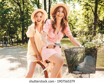 Two young beautiful smiling hipster woman in trendy summer sundress. Carefree women riding retro bicycle. Positive models having fun on bike posing in the park in hats. Best friends outdoors