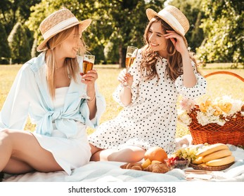 Two young beautiful smiling hipster female in summer sundress and hats.Carefree women making picnic outside.Positive models sitting on plaid on grass,drinking champagne, eating fruits and cheese