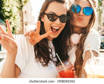 Two young beautiful smiling hipster female in trendy summer clothes. Carefree women posing outdoors.Positive models holding and drinking fresh cocktail smoothie drink in plastic cup with straw