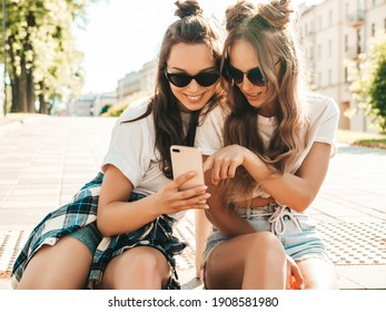 Two young beautiful smiling hipster female. Sexy carefree women sitting at the stairs in the street in sunglasses.Models having fun.They looking at cellphone screen laughing enjoying using mobile apps