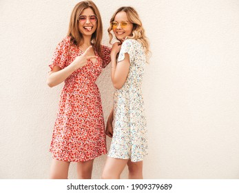 Two young beautiful smiling hipster female in trendy summer sundress.Sexy carefree women posing on the street background. Positive models having fun and hugging