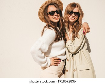 Two young beautiful smiling hipster female in trendy white sweater and coat. Sexy carefree women posing on  the street background in hat. Positive models having fun in sunglasses