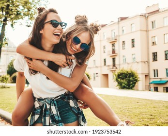 Two young beautiful smiling hipster female in trendy summer white t-shirt clothes.Sexy carefree women posing on street background. Model jumping on her friend back, gives piggyback riding outdoors - Shutterstock ID 1923753542