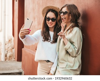 Two young beautiful smiling hipster female in trendy white sweater and coat. Sexy carefree women posing near red wall in the street in hat. Positive models having fun. They taking selfie photos