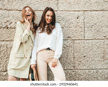Two young beautiful smiling hipster female in trendy white sweater and coat. Sexy carefree women posing on street background in hat. Positive models having fun. Communicating