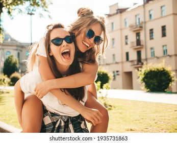Two young beautiful smiling hipster female in trendy summer white t-shirt clothes.Sexy carefree women posing on street background. Model jumping on her friend back, gives piggyback riding outdoors - Shutterstock ID 1935731863
