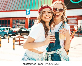 Two young beautiful smiling hipster female in trendy summer clothes.Sexy carefree women posing outdoors.Positive models holding and drinking fresh cocktail smoothie drink in plastic cup with straw - Shutterstock ID 1935731953