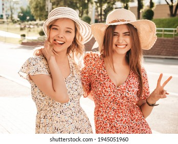Two young beautiful smiling hipster female in trendy summer sundress.Sexy carefree women posing on the street background in hats. Positive models having fun and hugging - Shutterstock ID 1945051960