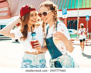 Two young beautiful smiling hipster female in trendy summer clothes.Sexy carefree women posing outdoors.Positive models holding and drinking fresh cocktail smoothie drink in plastic cup with straw - Shutterstock ID 1947777463