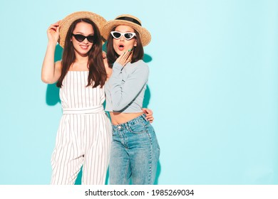 Two young beautiful smiling hipster female in trendy summer  clothes.Sexy carefree women posing near light blue wall in studio.Positive and cheerful models in hats - Shutterstock ID 1985269034