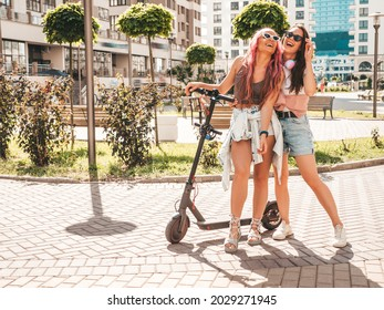 Two young beautiful smiling hipster female in trendy summer clothes.Sexy carefree women posing in the street with pink hair. Positive pure models having fun at sunset. Using electric Kick scooter - Shutterstock ID 2029271945