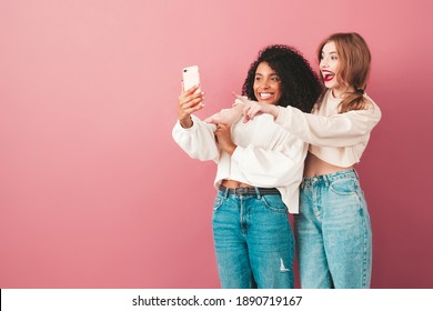 Two young beautiful smiling international hipster female in trendy summer jeans clothes. Sexy carefree women posing near pink wall in studio. Positive models having fun. They taking selfie photos