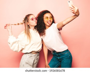 Two young beautiful smiling international hipster female in trendy summer clothes. Sexy carefree women posing near pink wall in studio. Positive models having fun. Concept of friendship.Taking selfie