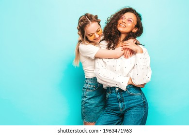 Two young beautiful smiling international hipster female in trendy summer clothes. Sexy carefree women posing near blue wall in studio. Positive models having fun. Concept of friendship