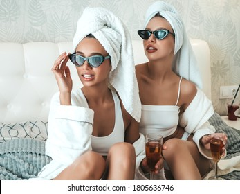 Two young beautiful smiling women in white bathrobes and towels on head. Sexy carefree models sitting on bed in posh apartment or hotel room. They drinking champagne at bachelorette party
