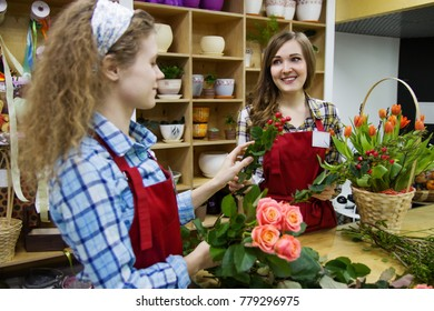 Two young beautiful smiling women florist are working with flowers  together in florist shop