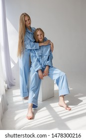 two young beautiful twin sisters posing in blue suits on white studio cyclorama in pattern of light and shadow near window. one of them sits on wooden cube, second stands and hugs her behind shoulders