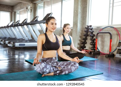Two young beautiful woman practicing yoga doing Sukhasana exercise
