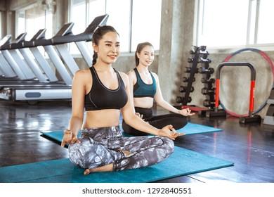Two young beautiful woman practicing yoga doing Sukhasana exercise