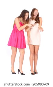 Two young beautiful woman smiling and pointing down over white background