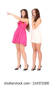 Two young beautiful woman smiling and pointing left over white background