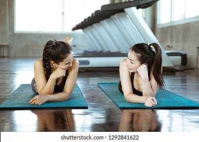 Two young beautiful woman talk and relax in gym