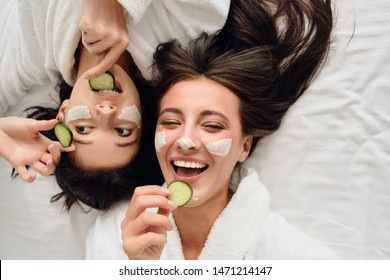 Two young beautiful women with dark hair in white bathrobes lying in bed with cosmetic mask on faces happily eating slices of cucumber together in modern cozy hotel