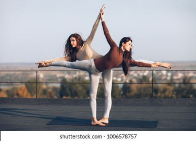 Two young beautiful women doing yoga asana virabhadrasana helping each other on the roof outdoor. partner yoga. Balance, concentration, equilibrium concept