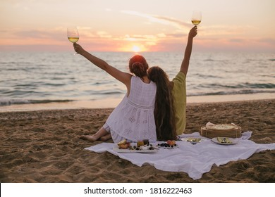 Two young beautiful women female friends having picnic with wine, pizza, cheese and fresh fruits on beach at sunset.
