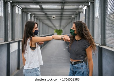 Two young beautiful women meet in the city and greet each other with arm for limited contagion from Coronavirus, Covid-19 - Millennial having fun together with facial mask after the lockdown