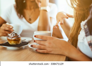 Two young and beautiful women meet at the bar for a cappuccino and to chat. A woman speaks gesturing while the other is listening