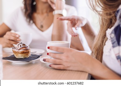 Two young beautiful women meet at the bar for cappuccino and to chat